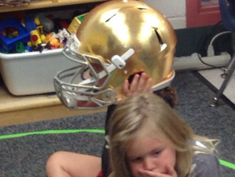 Little kid trying on an NDFB Helmet